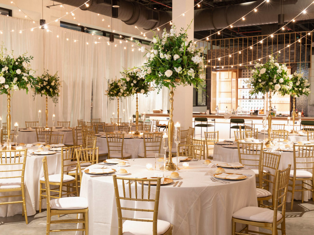 Traditional Classic Wedding Reception Decor, Round Tables with Gold Chiavari Chairs, Tall Gold Greenery and White Floral Centerpieces, Hanging String Lights | Tampa Bay Wedding Venue Hyde House