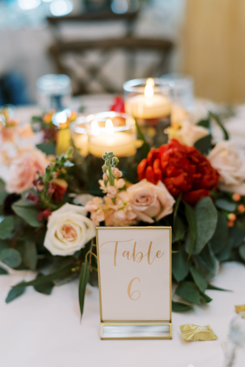 Rustic Romantic Wedding Reception Decor, Low Blush Pink, Ivory, Red Florals and Greenery Wreath Centerpiece with Candles, Gold Table Number Signage   Tampa Bay Wedding Rentals A Chair Affair