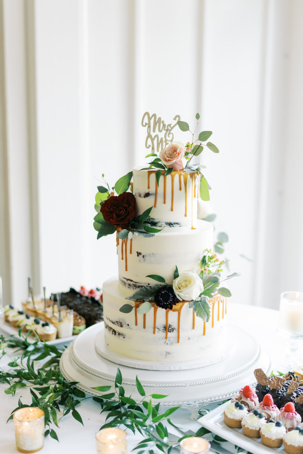White Semi Naked Three Tier Gold Drip Wedding Cake with Dark Purple and Ivory Roses and Greenery, Gold Cake Topper   Tampa Bay Wedding Cake The Artistic Whisk