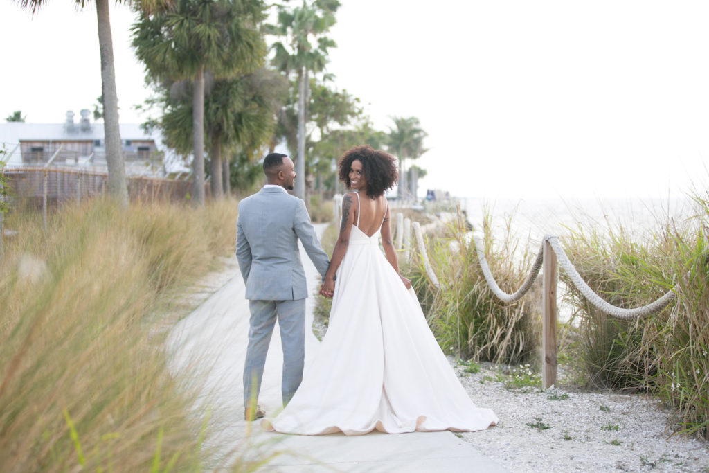 Modern Tropical Bride and Groom Walking On South Tampa Waterfront | Tampa Bridal Attire Store Truly Forever Bridal | Tampa Bay Wedding Photographer Carrie Wildes Photography