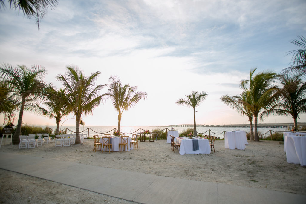 Modern Tropical Tampa Bay Waterfront Sunset Wedding Reception on the sand, Sunset Outdoor Reception with White Linens and Bamboo Inspired Crossback Chairs | Tampa Bay Wedding Planner Socialite Events | Florida Wedding Photographer Carrie Wildes Photography