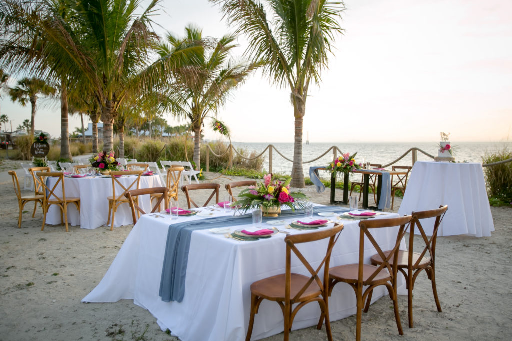 Modern Tropical Tampa Bay Waterfront Sunset Wedding Reception on the sand, Sunset Outdoor Reception with White Linens and Bamboo Inspired Crossback Chairs, Dusty Blue Table Runner, Bright Pink Table Napkins| Tampa Bay Wedding Planner Socialite Events | Florida Wedding Photographer Carrie Wildes Photography