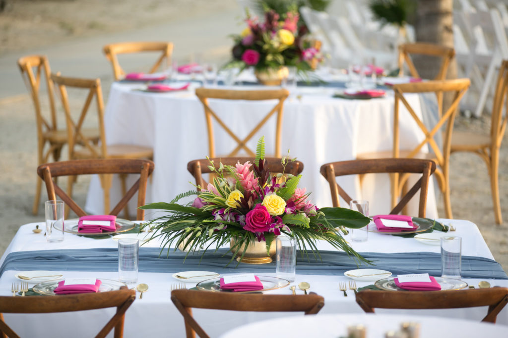 Modern Tropical Wedding Reception Decor, South Tampa Salt Shack On the Bay Private Beachfront | Round Tables with Low Floral Vibrant Centerpieces, Monstera Leaf Place Setting, Clear Acrylic Charger With Gold Foil Rim and Gold Flatware, Bright Pink Napkin with White Menu with Gold Lettering | Tampa Bay Wedding Planners Socialite Events | Central Florida Wedding Photographer Carrie Wildes Photography