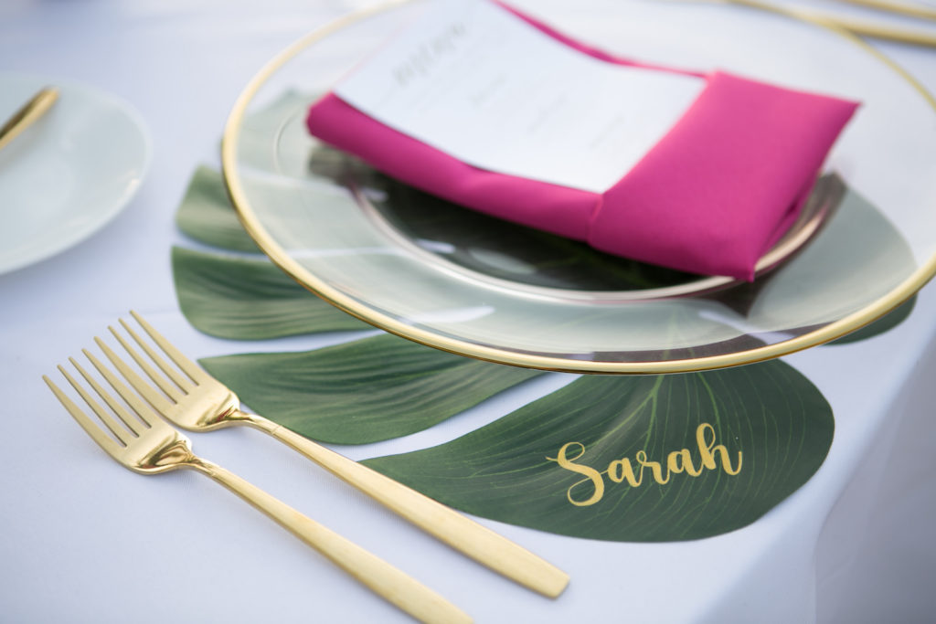 Modern Tropical Wedding Place Setting, Florida Wedding Reception Decor and Styling. Clear Acrylic Charger With Gold Foil Rim and Gold Flatware, Bright Pink Napkin with White Menu with Gold Lettering, Monstera Leaf Place Setting with Custom Gold Name Calligraphy | Tampa Bay Wedding Planners Socialite Events | Central Florida Wedding Photographer Carrie Wildes Photography