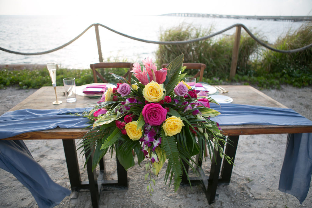 Florida Sweetheart Table at Florida Wedding Reception with Modern Tropical Decor, Vibrant Pink, Yellow and Green Bouquet with Dusty Blue Table Runner | South Tampa Private Beachfront Salt Shack On the Bay | Florida Sunset Wedding Photographer Carrie Wildes Photography | SocialiteEvents