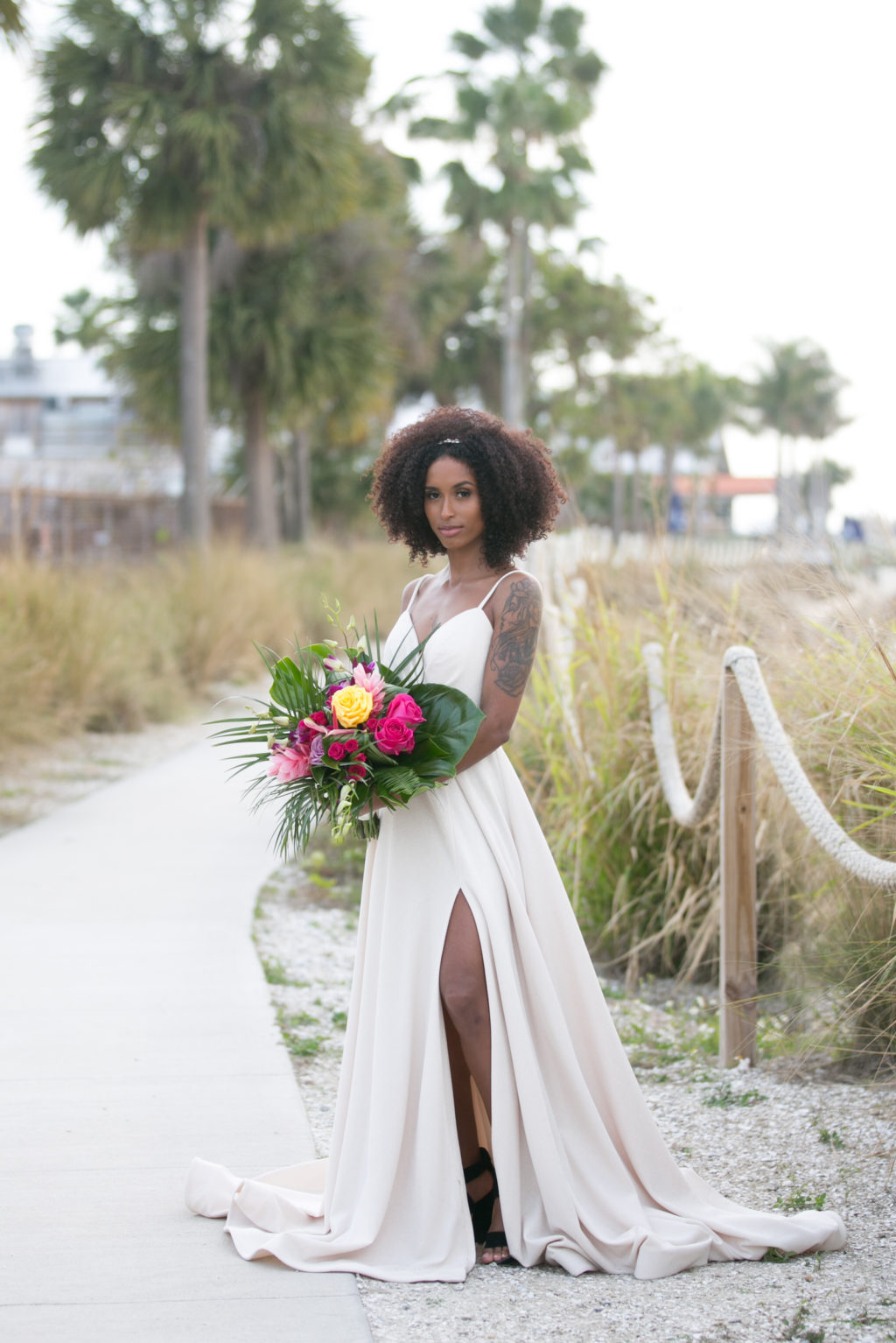Boho Florida Bride Wearing Elegant Flowy Wedding Dress with High Slit, Holding Modern Tropical Inspired Floral Bouquet with Vibrant Yellow Roses, Bright Pink Flowers, Monstera and Palm Leaves | Salt Shack On the Bay Wedding | Tampa Bay Wedding Photographer Carrie Wildes Photography | South Tampa Wedding Planners Socialite Events | Wedding Dress Boutique Truly Forever Bridal Tampa
