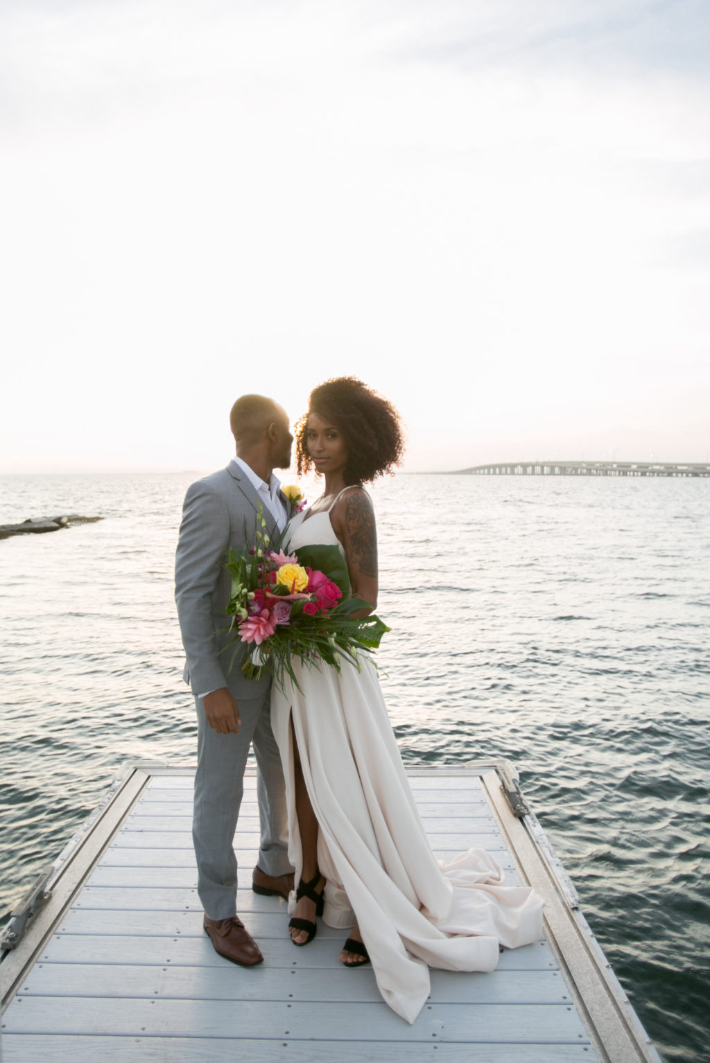 Modern Tropical Inspired Florida Bride and Groom, On Waterfront Pier in Boho Off-White Dress with High Slip, Holding Vibrant Bridal Bouquet | Salt Shack On the Bay Wedding Styled Shoot | Tampa Bay Wedding Photographer Carrie Wildes Photography | South Tampa Wedding Planner Socialite Events