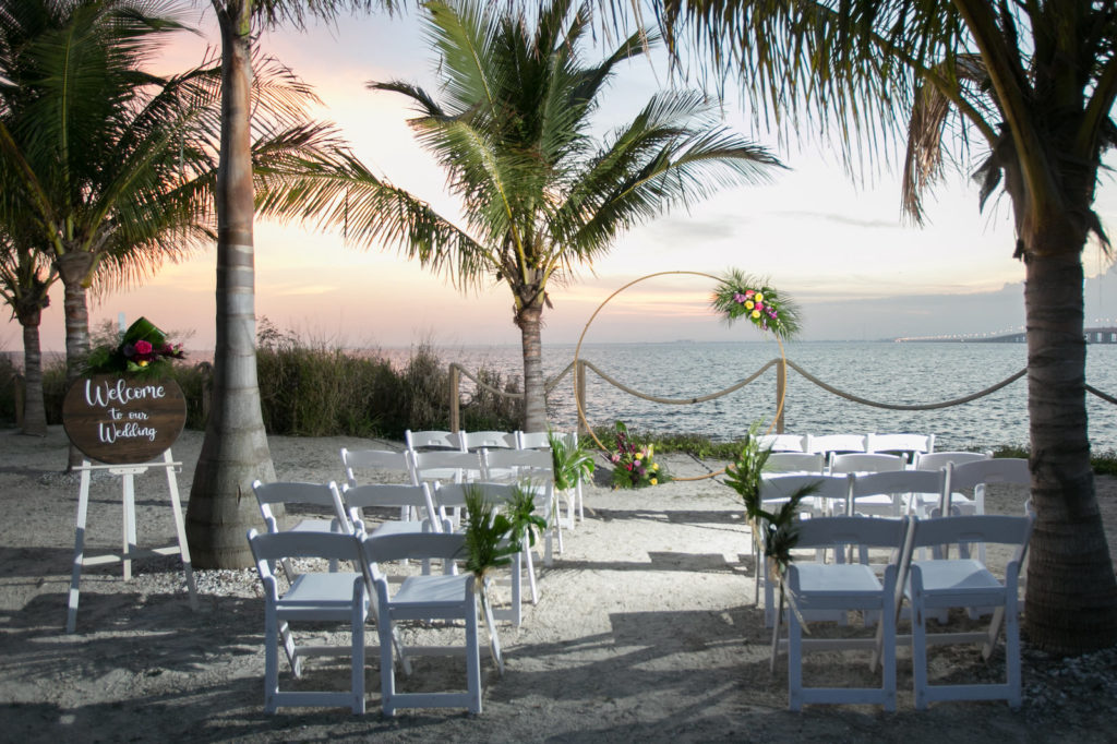 Sunset Waterfront Florida Wedding Ceremony on the sand, Tropical Wedding Decor with Modern Circle Arch | Tampa Bay Wedding Photographer Carrie Wildes Photography | South Tampa Wedding Planners Socialite Events