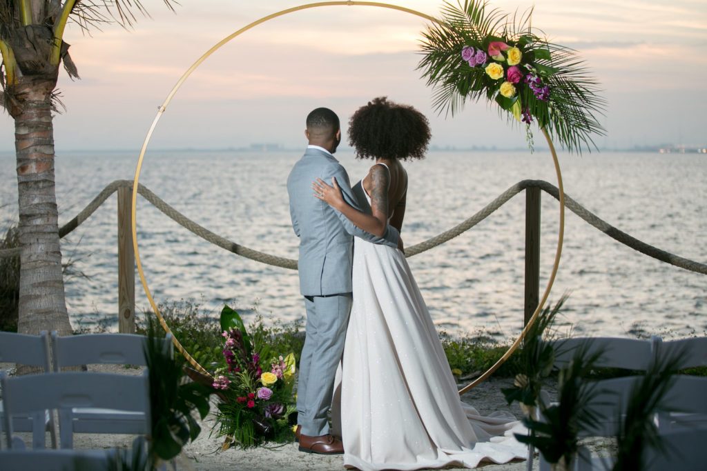Sunset Waterfront Florida Wedding Ceremony with Bride and Groom on the sand, Tropical Wedding Decor with Modern Circle Arch | Tampa Bay Wedding Photographer Carrie Wildes Photography | South Tampa Wedding Planners Socialite Events