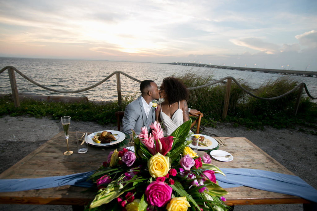 Florida Bride and Groom Kiss at Sweetheart Table at Sunset Florida Wedding Reception with Modern Tropical Decor, Vibrant Pink, Yellow and Green Bouquet with Dusty Blue Table Runner | South Tampa Private Beachfront Salt Shack On the Bay | Florida Sunset Wedding Photographer Carrie Wildes Photography | SocialiteEvents