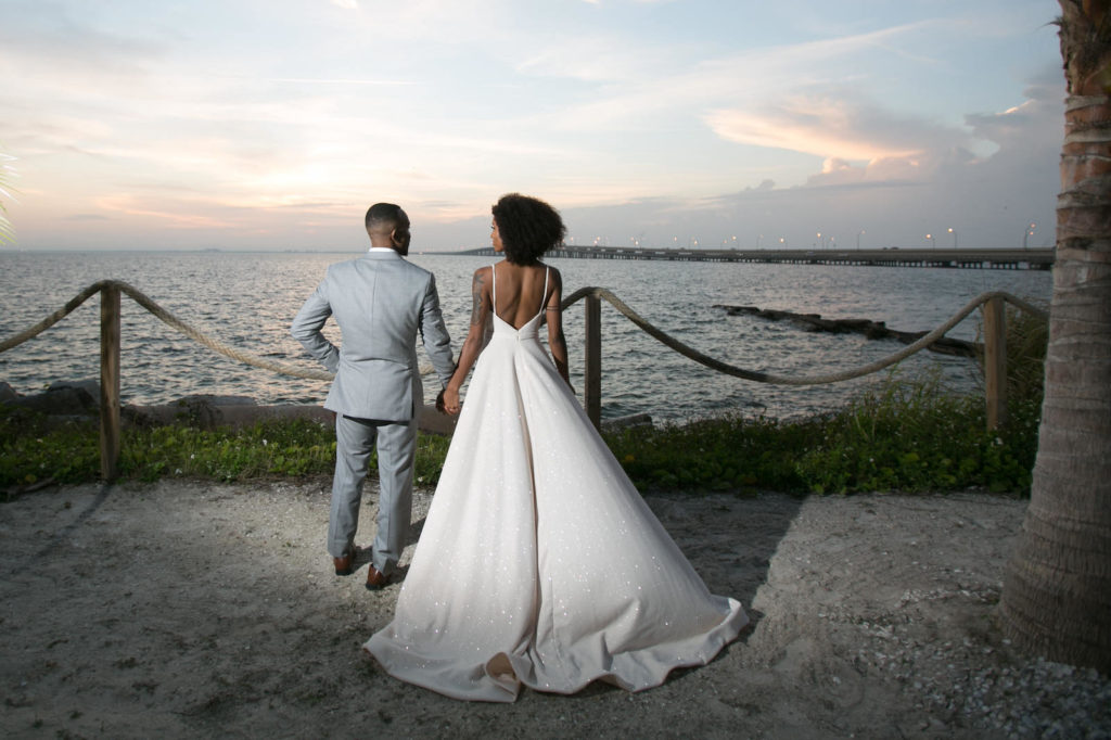Modern Tropical Inspired Florida Bride and Groom at Sunset, On Waterfront Pier in Boho Off-White Dress with High Slip | Salt Shack On the Bay Wedding Styled Shoot | Tampa Bay Wedding Photographer Carrie Wildes Photography | South Tampa Wedding Planner Socialite Events | Truly Forever Bridal