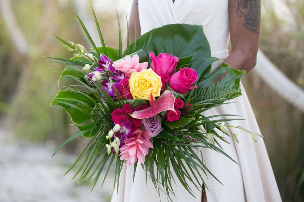Boho Florida Bride Wearing Elegant Flowy Wedding Dress, Holding Modern Tropical Inspired Floral Bouquet with Vibrant Yellow Roses, Bright Pink Flowers, Purple Hibiscus, Monstera, and Palm Leaves | Tampa Bay Wedding Photographer Carrie Wildes Photography | South Tampa Wedding Planners Socialite Events | Wedding Dress Boutique Truly Forever Bridal Tampa