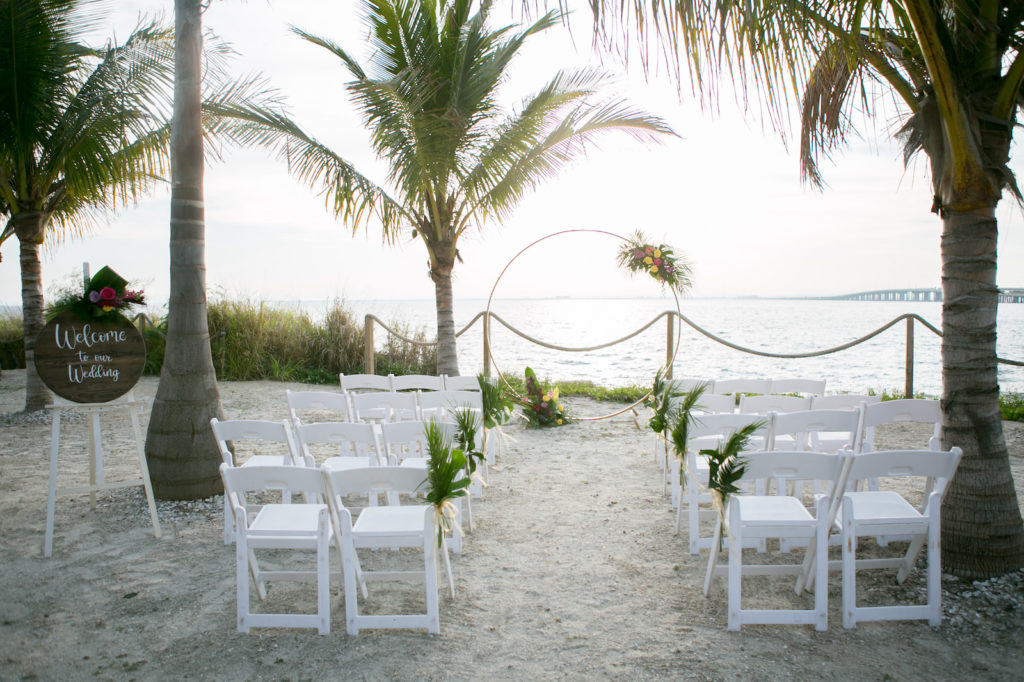 South Tampa Waterfront Intimate Wedding Ceremony on the Sand with Minimalist Gold Circle Arch, Modern Tropical Wedding Decor with Wooden Welcome to our Wedding Sign with Vibrant Yellow Roses, Bright Pink Flowers, Purple Hibiscus, Monstera, and Palm Leaves | Tampa Bay Wedding Photographer Carrie Wildes Photography | South Tampa Wedding Planners Socialite Events | Salt Shack On the Bay Wedding