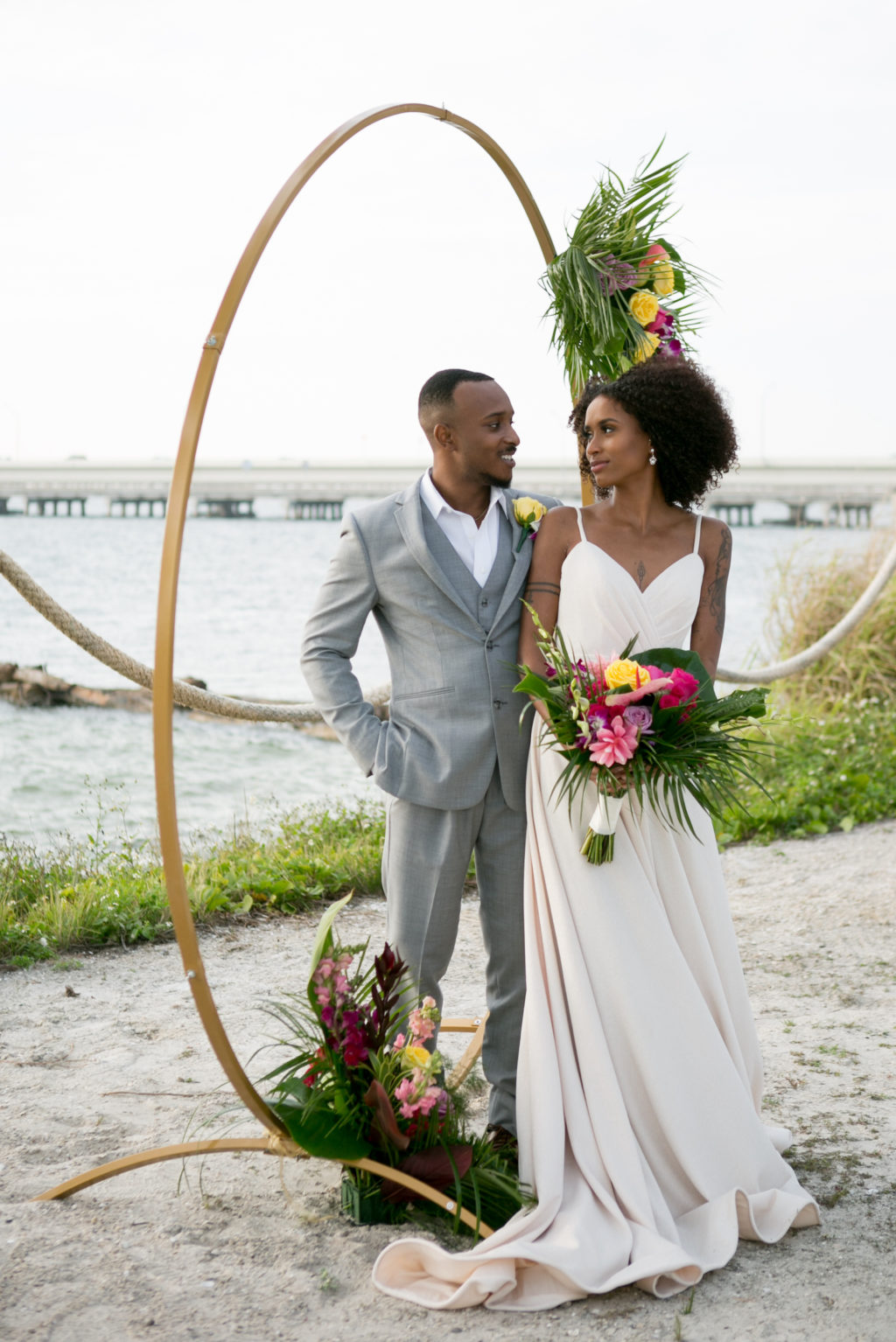 South Tampa Waterfront Intimate Wedding Ceremony on the Sand with Minimalist Gold Circle Arch, Boho Inspired Bride and Groom with Neutral Tone Attire, Bride Holding Modern Tropical Wedding Bouquet with Vibrant Yellow Roses, Bright Pink Flowers, Purple Hibiscus, Monstera, and Palm Leaves | Tampa Bay Wedding Photographer Carrie Wildes Photography | South Tampa Wedding Planners Socialite Events | Salt Shack On the Bay Wedding