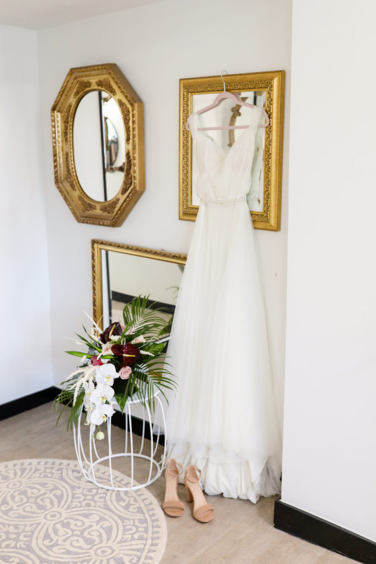 Boho Tulle Wedding Dress Hanging on Frame, Tropical White Orchids and Burgundy Floral with Palm Fronds Bouquet, Nude Wedding Shoes | Tampa Bay Wedding Photographer Lifelong Photography Studio | Wedding Florist Iza's Flowers