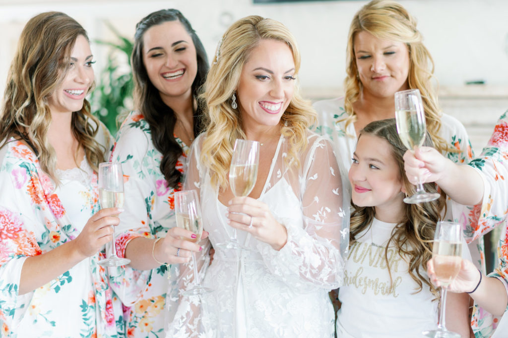 Tampa Bay Bride Wearing White Illusion Cover Up and Bridesmaids in Floral Robes Cheering with Champagne   Wedding Hair and Makeup Michele Renee the Studio