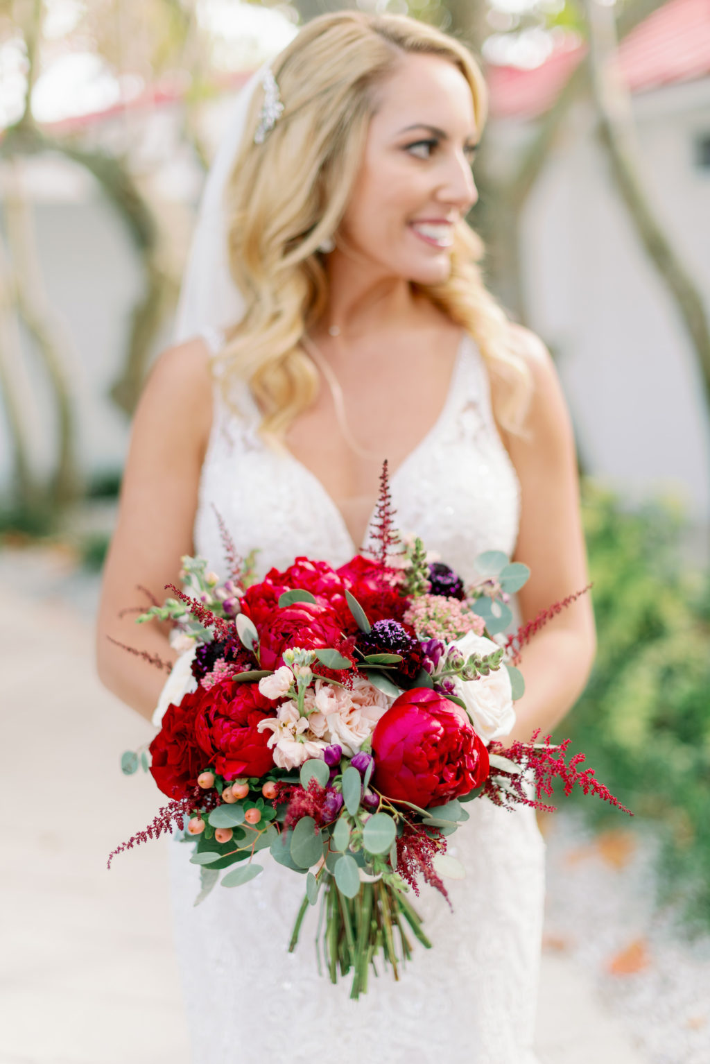 Florida Bride in Lace Wedding Dress Holding Bright Colorful Red, Ivory and Greenery Eucalyptus Floral Bouquet   Tampa Bay Wedding Hair and Makeup Michele Renee the Studio