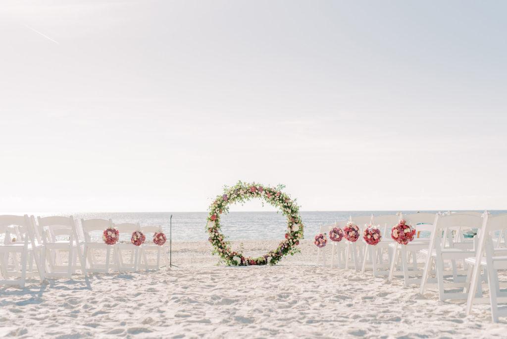 Elegant Beach Wedding Ceremony Decor, White Folding Chairs, Round Greenery and White, Pink Floral Arch | Tampa Bay Wedding Photographer Kera Photography | Waterfront Wedding Venue Ritz Carlton Sarasota