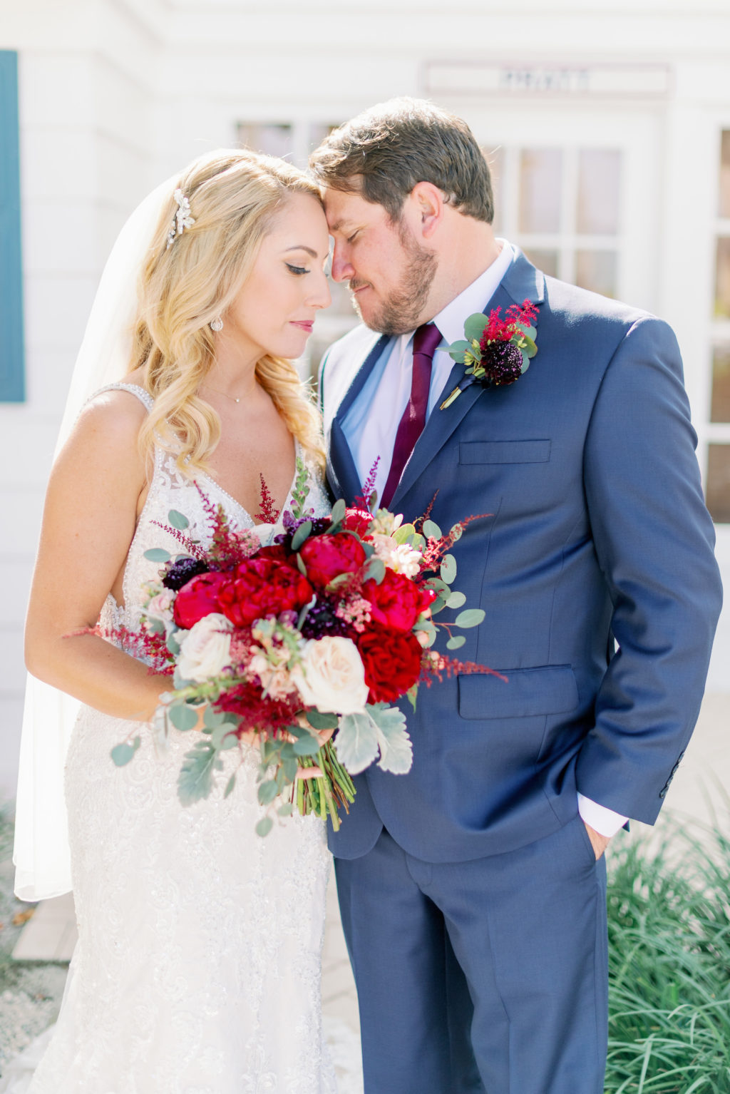 Romantic Rustic Glam Bride in Lace Wedding Dress Holding Red, Ivory and Greenery Floral Bouquet and Groom in Blue Suit   Tampa Bay Wedding Hair and Makeup Michele Renee the Studio