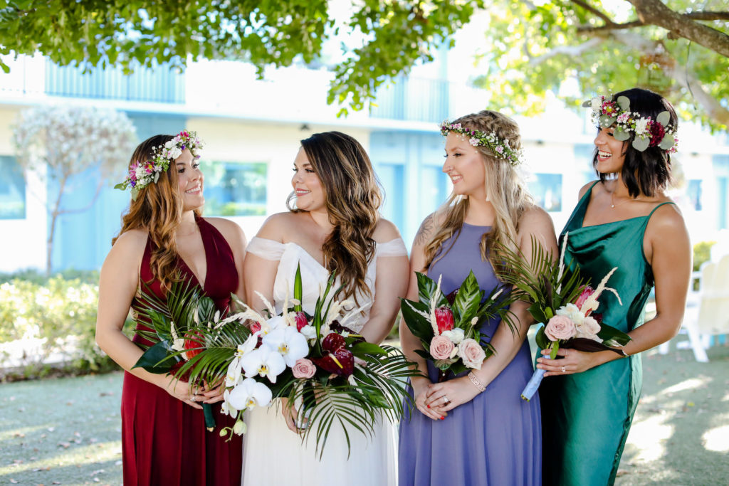 Florida Bride Wearing Off the Shoulder Tulle and Chantilly Lace Dreamy Boho Wedding Dress Holding Tropical White Orchid, Burgundy Red Anthuriums, Palm Fronds Floral Bouquet, Bridesmaids in Mix and Match Merlot Red, Purple, and Teal Long Dresses and Flower Crowns | Tampa Bay Wedding Photographer Lifelong Photography Studio | St. Pete Beach Wedding Venue Postcard Inn | Wedding Florist Iza's Flowers