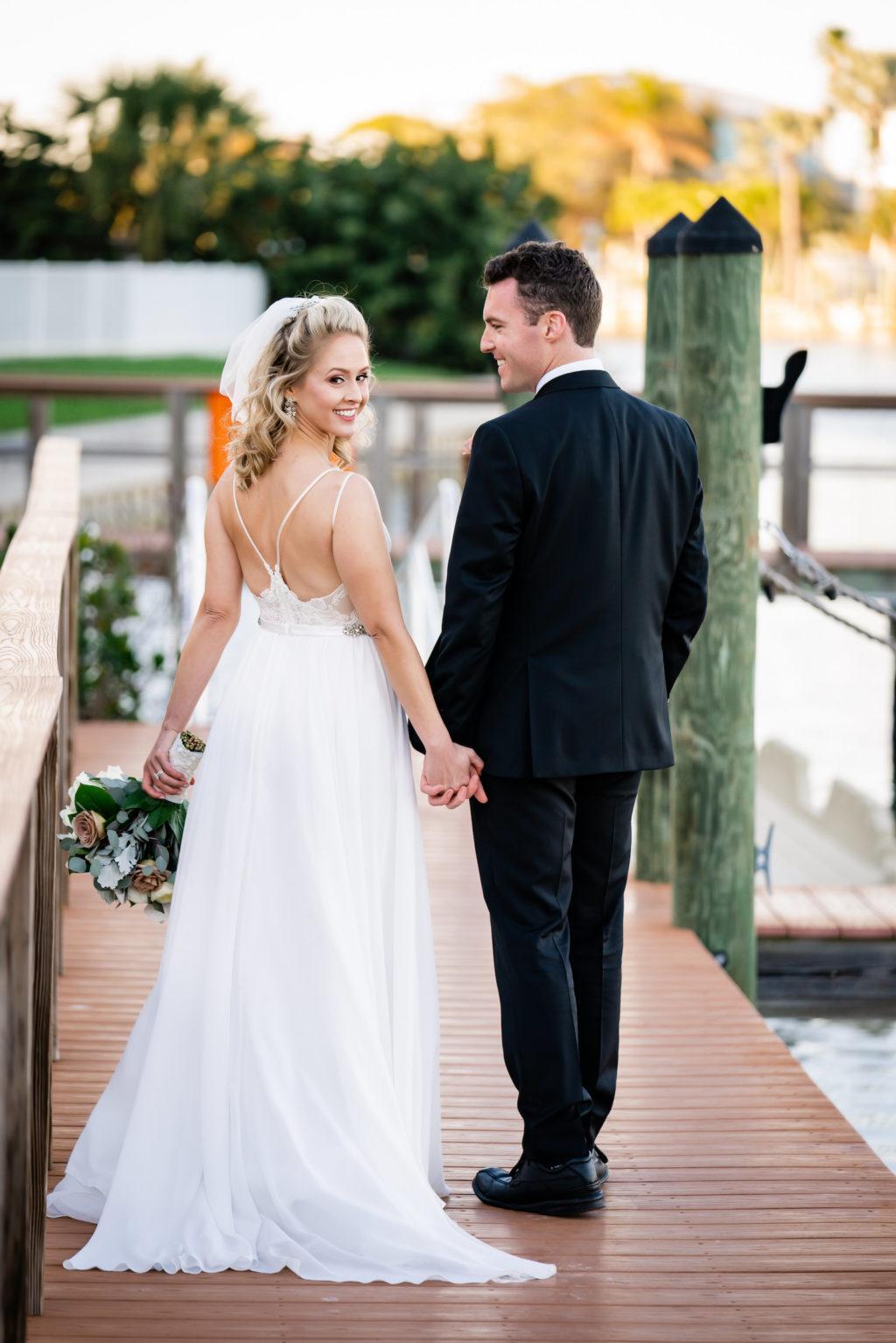 Florida Bride and Groom Holding Hands on Dock | St. Pete Wedding Venue Hotel Zamora | Tampa Wedding Dress Isabel O'Neil Bridal