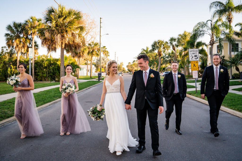 Florida Bride in A-Line Spaghetti Strap, Lace Bodice and Rhinestone Belt Wedding Dress Holding Hands with Groom, Bridesmaids in Matching Mauve Dresses, Groomsmen in Purple Ties and Black Suits | Tampa Bay Wedding Florist Iza's Flowers | Wedding Dress Isabel O'Neil Bridal