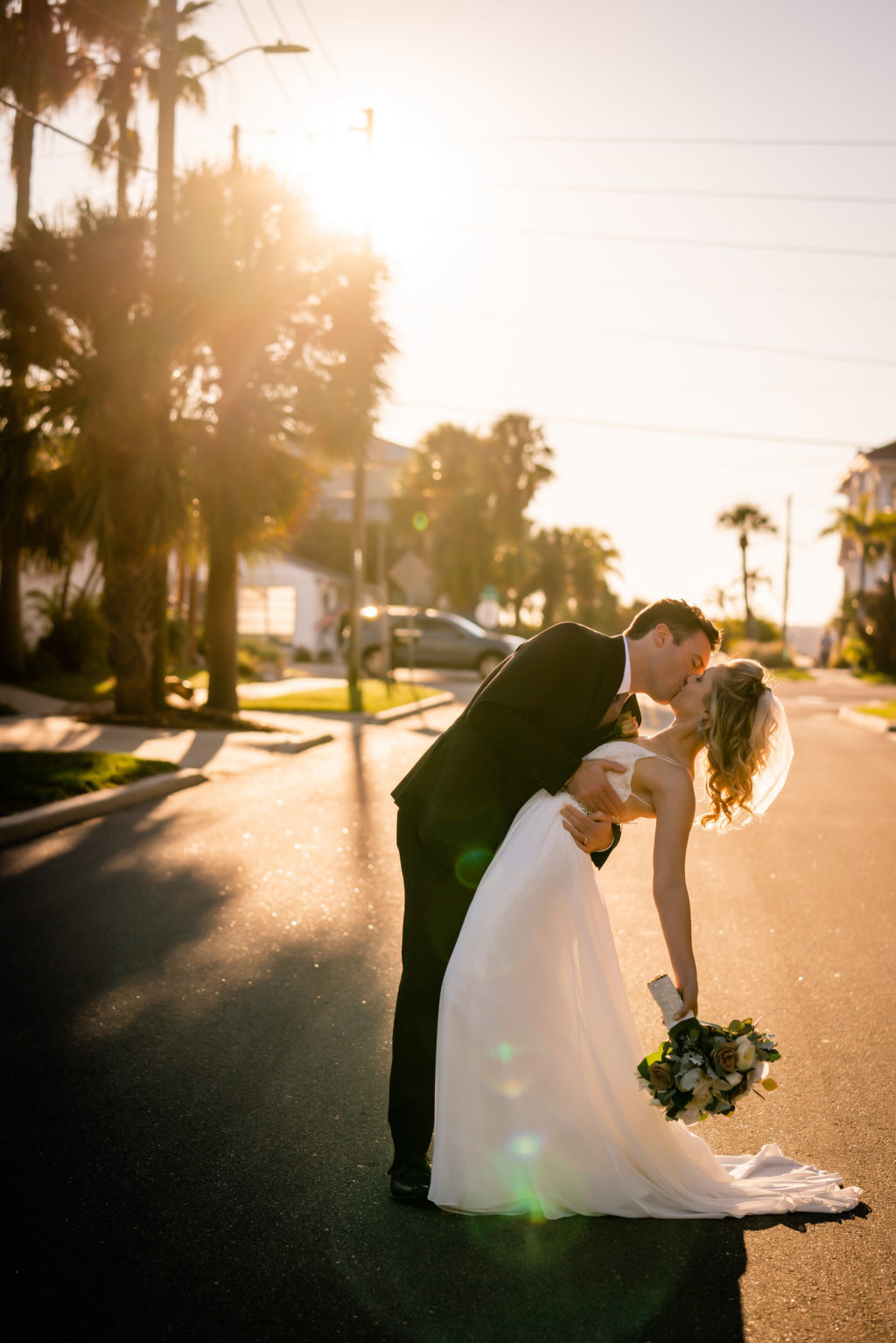 Romantic Groom Dip Kissing Bride Sunset on the Street Wedding Photo | Tampa Bay Wedding Dress Isabel O'Neil Bridal