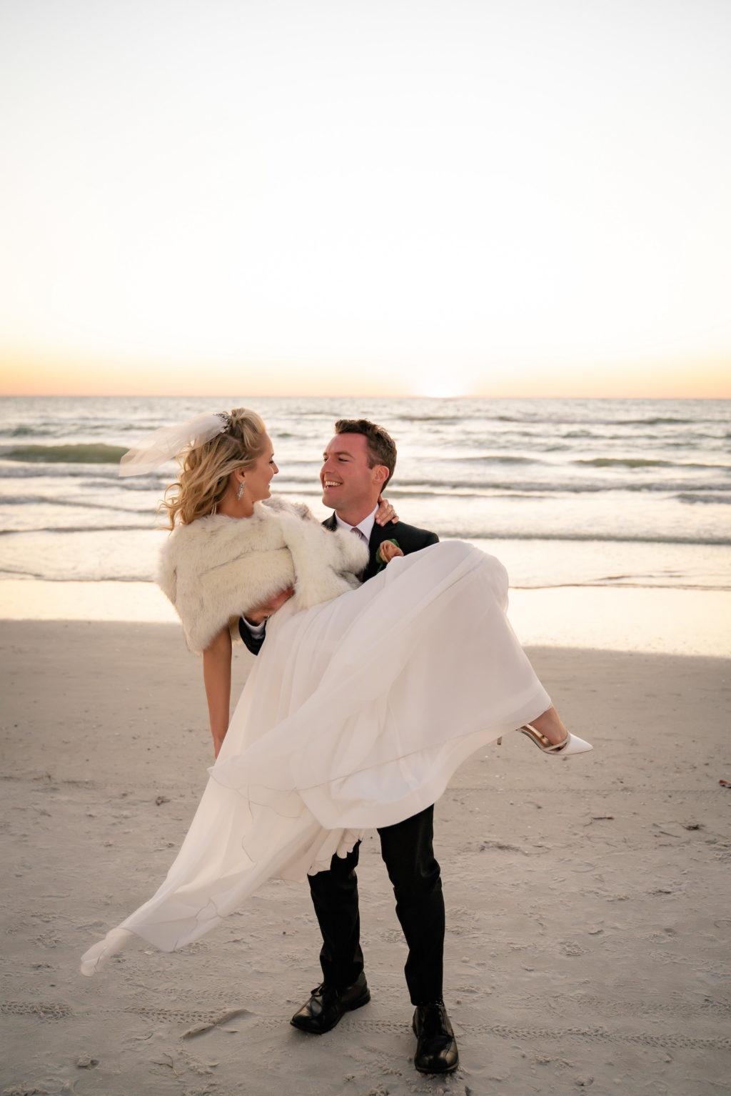 Groom Carrying Bride Wearing White Fur Shawl on Beach | Tampa Bay Wedding Dress Isabel O'Neil Bridal