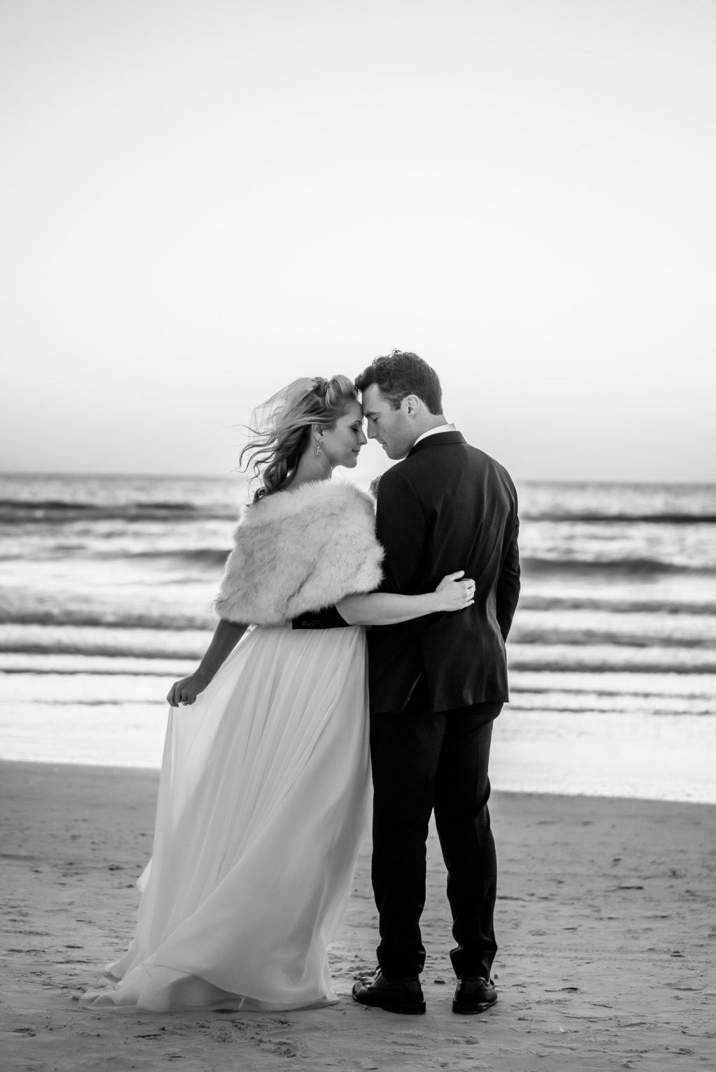 Black and White Groom and Bride Wearing White Fur Shawl on Beach | Tampa Bay Wedding Dress Isabel O'Neil Bridal | Florida Beach Wedding Portraits