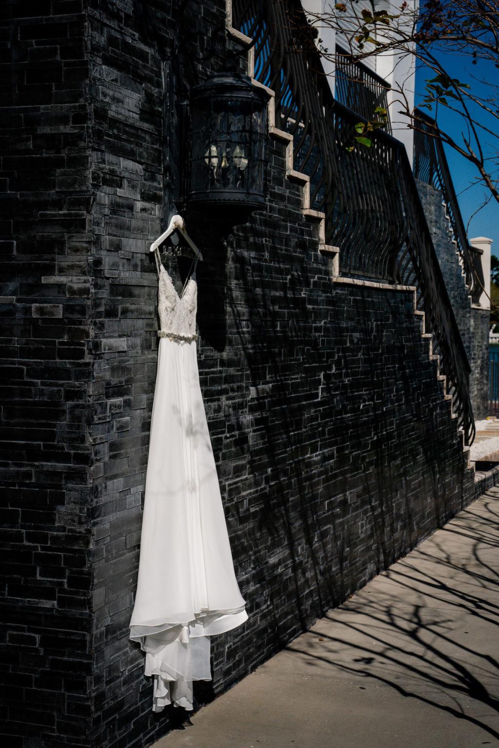A-Line Spaghetti Strap Lace Bodice with Rhinestone Belt Alyne by Rita Vinieris Wedding Dress Hanging on Black Brick Wall | St. Pete Wedding Venue The Hotel Zamora | Wedding Dress Isabel O'Neil Bridal