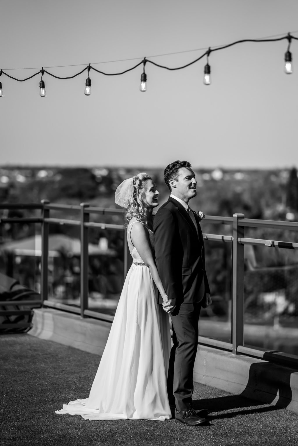 Romantic Intimate Bride Holding Hands with Groom from Behind on Rooftop Waterfront St. Pete Wedding Venue Hotel Zamora | Tampa Wedding Dress Isabel O'Neil Bridal | First Touch Wedding Portrait