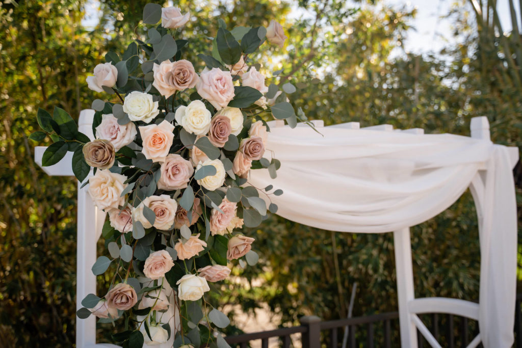 Mauve, Blush Pink, Ivory Roses and Eucalyptus Greenery Floral Arrangement on White Pergola Style Arch with Linen Draping | Tampa Bay Wedding Florist Iza's Flowers