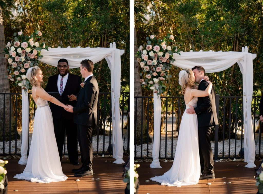Florida Bride and Groom Exchanging Wedding Vows During Outdoor Courtyard Ceremony, White Pergola Style Arch with Linen Draping, Mauve and Ivory Roses, Eucalyptus Greenery Floral Arrangement | St. Pete Wedding Venue Hotel Zamora | Tampa Wedding Florist Iza's Flowers