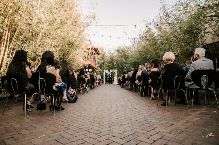 Industrial Inspired Florida Wedding Ceremony in Bamboo Garden Courtyard, Decorated with Romantic Moody Florals, Ceremony Arch with Soft White Draping and Greenery | Tampa Bay's Best Place for a Wedding NOVA 535 in Downtown St. Pete