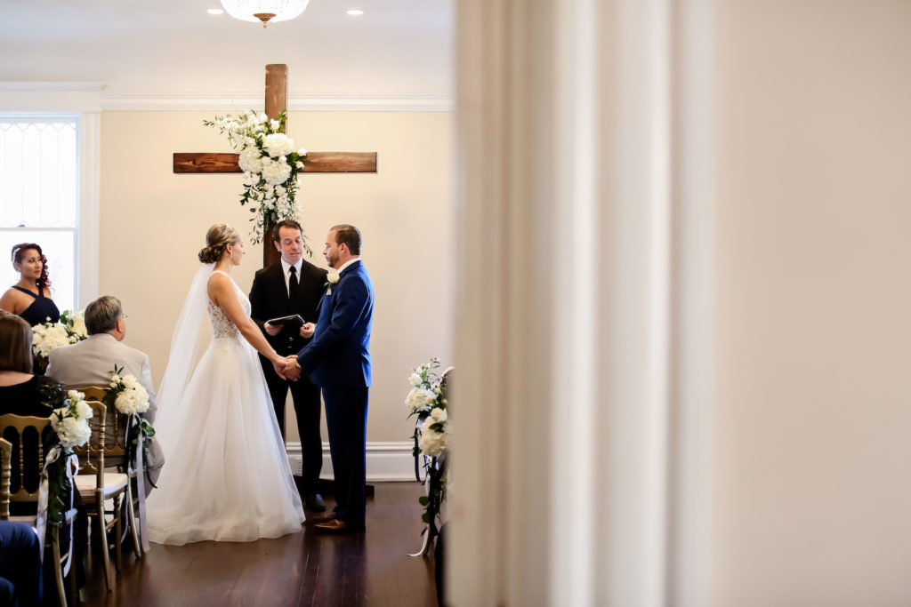 Classic Traditional Bride and Groom Exchanging Wedding Ceremony Vows at Wooden Cross Altar with White Floral Arrangements | Tampa Bay Wedding Photographer Lifelong Photography Studio | Wedding Planner Core Concepts | Wedding Rentals A Chair Affair | Kate Ryan Event Rentals