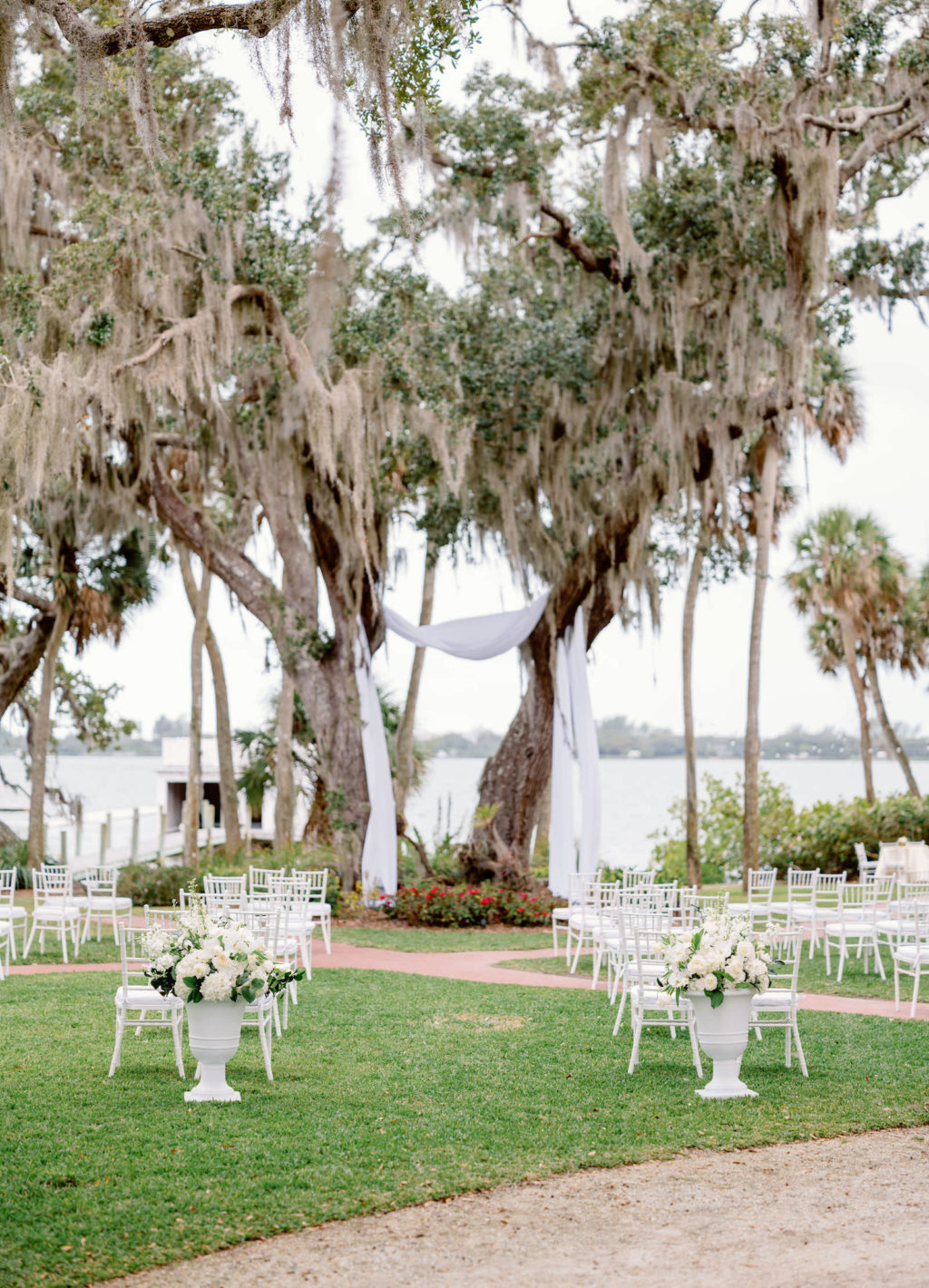 Elegant Luxurious Wedding Waterfront Ceremony Decor, White Chiavari Chairs, Large Vases with Floral Arrangements, Draping Hanging from Trees | Tampa Bay NK Productions Wedding Planning