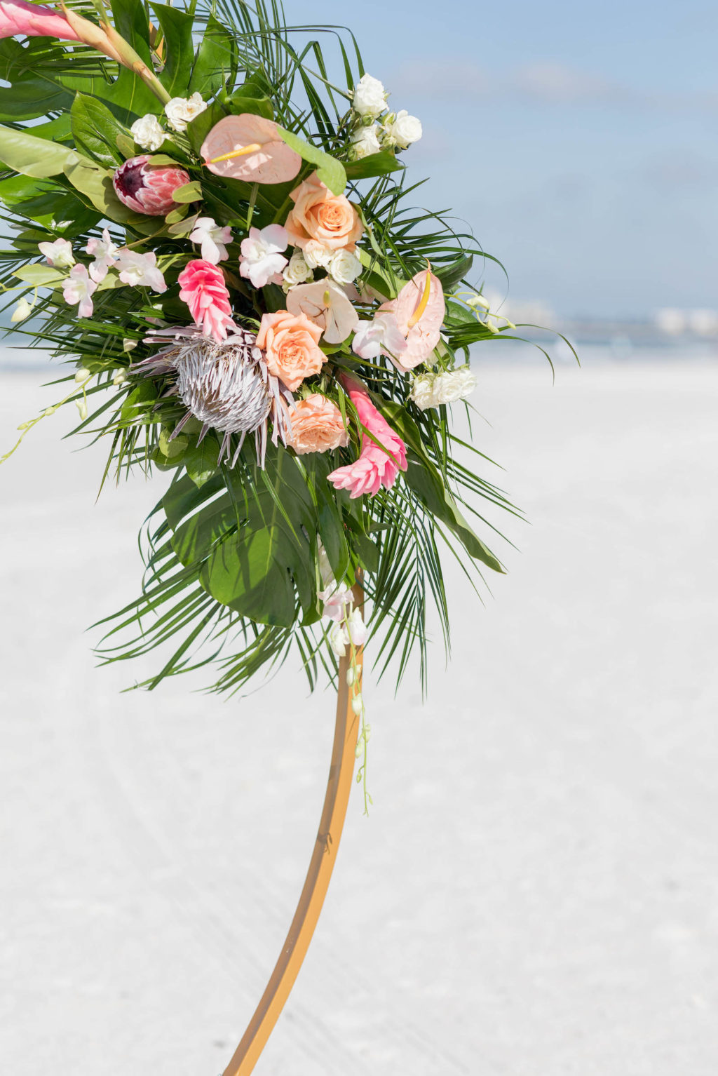 Beach Wedding Round Arch Floral Arrangement Spray | Tropical Wedding Flowers with Monstera Leaf Greenery, Peach Roses, White Anthurium, and Pink Protea