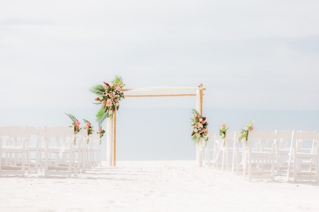 Tropical Wedding Ceremony Decor on the Beach, Bamboo Arch with Colorful Floral Arrangements, White Folding Chairs | Wedding Venue Hilton Clearwater Beach | Wedding Florist Iza's Flowers