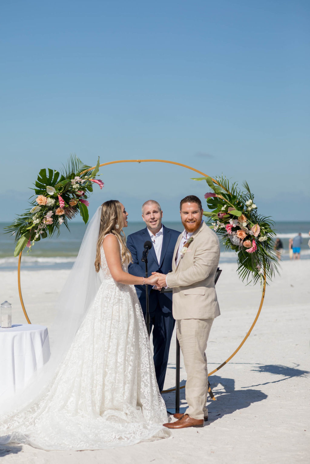 Bride and Groom Exchanging Vows during Outdoor Beach Wedding at St. Pete Beach Wedding Venue The Don CeSar Pink Palace | Monique Lhuillier Designer Wedding Dress A Line Ballgown Lace Bridal Gown | Groom Wearing Casual Khaki Suite | Beach Wedding Round Arch Floral Arrangement Spray | Tropical Wedding Flowers with Monstera Leaf Greenery, Peach Roses, White Anthurium, and Pink Protea