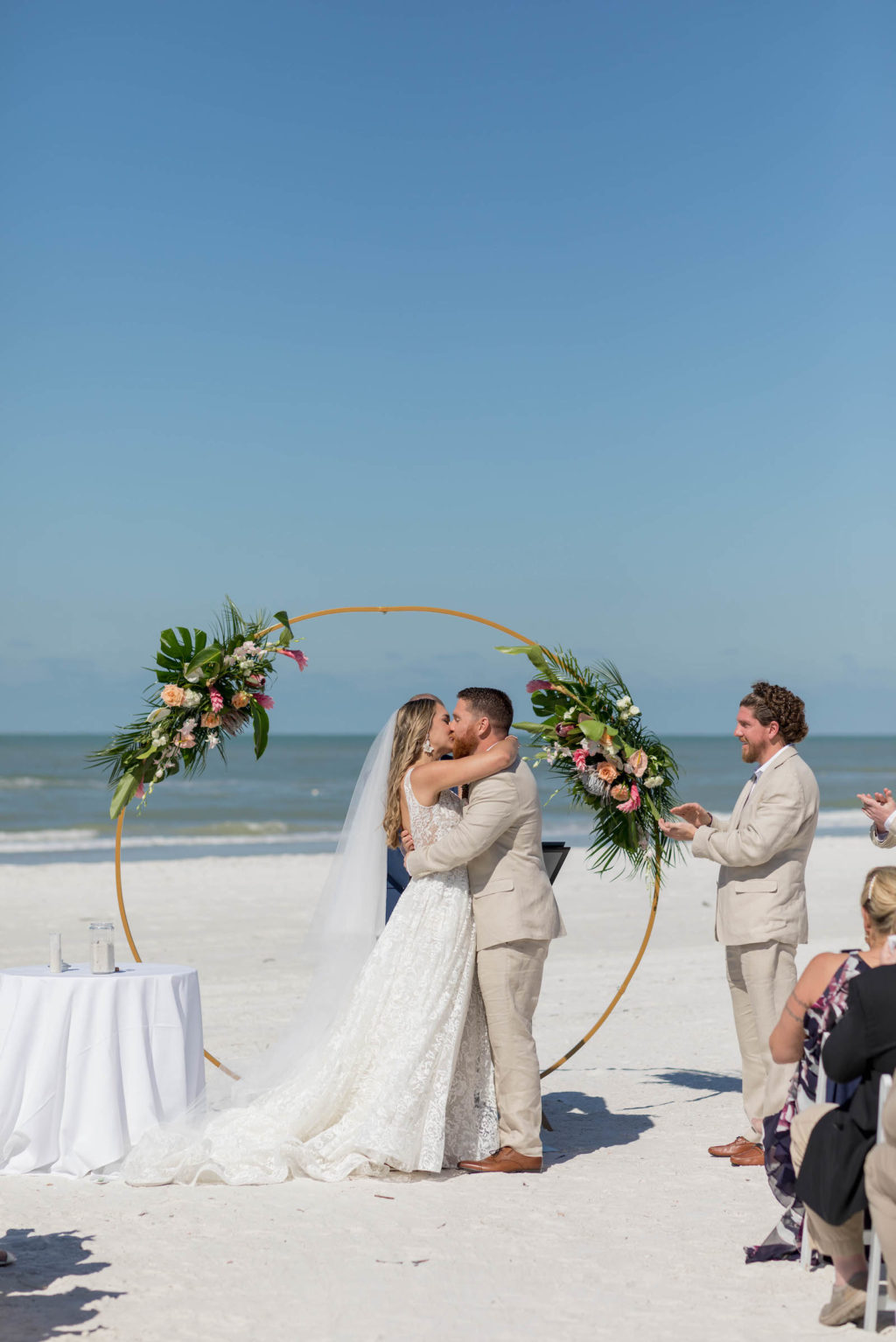 Bride and Groom First Kiss during Outdoor Beach Wedding at St. Pete Beach Wedding Venue The Don CeSar Pink Palace | Monique Lhuillier Designer Wedding Dress A Line Ballgown Lace Bridal Gown | Groom Wearing Casual Khaki Suite | Beach Wedding Round Arch Floral Arrangement Spray | Tropical Wedding Floral Arrangement with Monstera Leaf Greenery, Peach Roses, White Anthurium, and Pink Protea