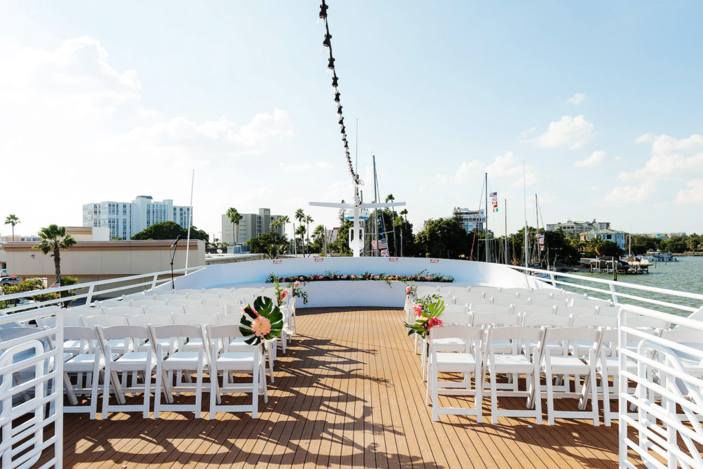 Tropical Waterfront Wedding Ceremony Decor, White Folding Chairs, Monstera Leaves and Pink Flower Arrangements   Tampa Bay Wedding Photographer Limelight Photography   Wedding Venue Yacht StarShip
