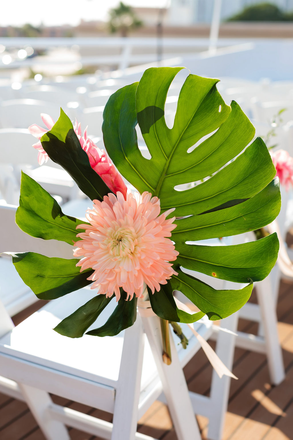 Tropical Wedding Ceremony Decor, Monstera Palm Leaf with Pink Flower Arrangement on Chair   Tampa Bay Wedding Photographer Limelight Photography   Waterfront Wedding Venue Yacht StarShip