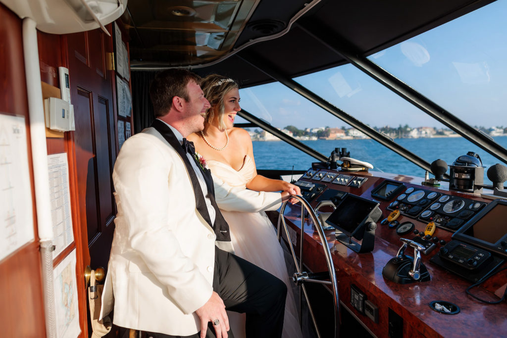 Florida Bride and Groom in White Tuxedo Driving Boat   Waterfront Wedding Venue Yacht Starship   Tampa Bay Wedding Photographer Limelight Photography