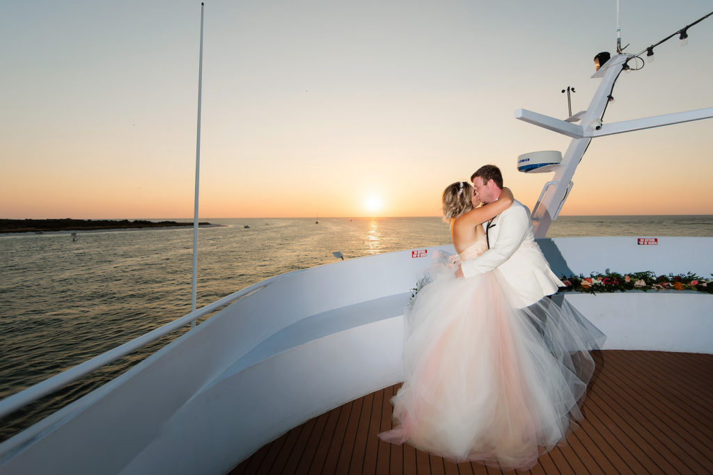 Sunset Romantic Bride in Blush Pink Strapless Princess Ballgown Tulle Skirt Wedding Dress and Groom in White Tuxedo on Deck of Boat   Waterfront Wedding Venue Yacht Starship   Tampa Bay Wedding Photographer Limelight Photography