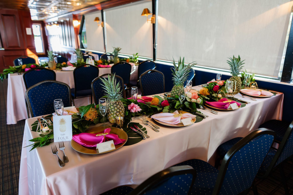 Tropical Wedding Reception Decor, Blush Pink Silk Linen Tables, Gold Chargers with Hot Pink Linen Napkins, Gold Accents, Pineapples and Colorful Flower and Palm Leaves Garland Centerpiece   Waterfront Wedding Venue Yacht StarShip   Tampa Bay Wedding Photographer Limelight Photography
