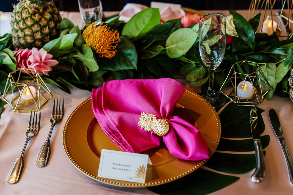 Tropical Wedding Reception Decor, Gold Chargers, Hot Pink Linen Napkin with Gold Pineapple Ring Holder, Geometric Gold Candle Holders, Greenery Leaves and Flower Table Runner Garland, Pineapples | Tampa Bay Wedding Photographer Limelight Photography