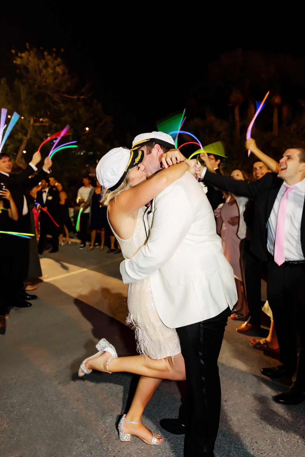 Nautical Bride in Short Wedding Reception Dress, Sailor Hat, and Groom in White Tuxedo with Sailor Hat Kissing During Glowsticks Wedding Exit   Tampa Bay Wedding Photographer Limelight Photography