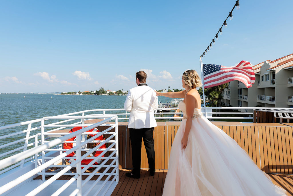 Florida Bride in Ballgown Strapless Wedding Dress with Tulle Skirt and Blush Pink Lining, Floral Belt First Look with Groom in White Tuxedo   Waterfront Wedding Venue Yacht StarShip   Tampa Bay Wedding Photographer Limelight Photography