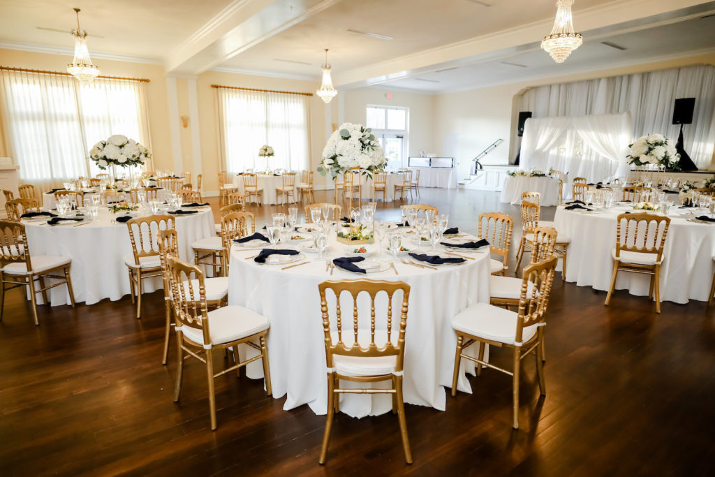 Classic Wedding Reception Decor, Gold Chairs, Round Tables with White Linens, Navy Blue Linen Napkins, Tall White Floral Centerpieces | Tampa Bay Wedding Photographer Lifelong Photography Studio | Wedding Rentals A Chair Affair | Kate Ryan Event Rentals | Wedding Venue The Orlo House| | Wedding Planner Core Concepts