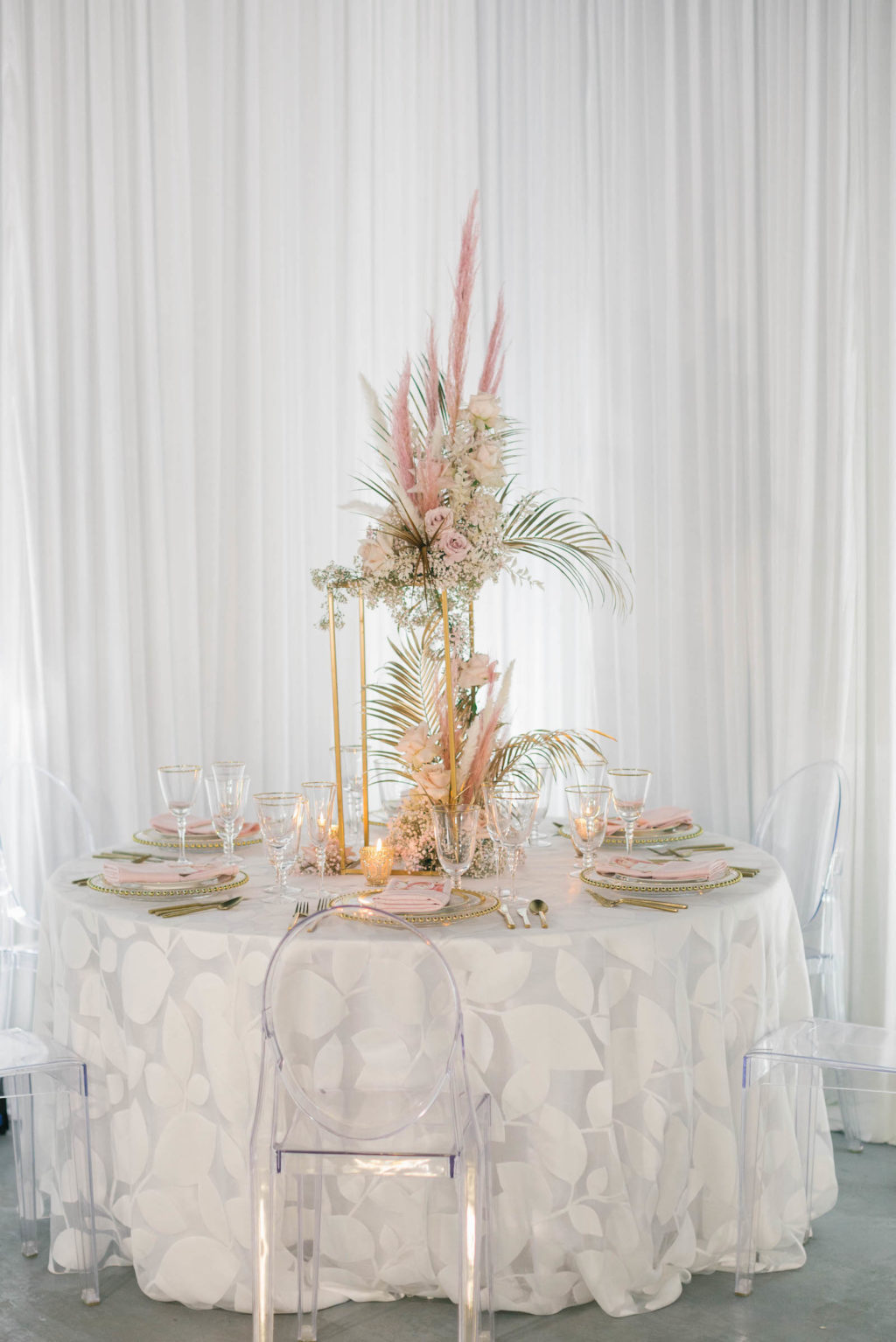 Clearwater Beach Wedding Venue Bellwether Beach Resort Styled With Love Something Bleu by McKenna Bleu | Instagram Wedding Designer Inspiration | Clear Ghost Chairs and White Botanical Print Reception Table Linen with Gold Boho Centerpiece with Pampas Grass Roses and Palm Leaves